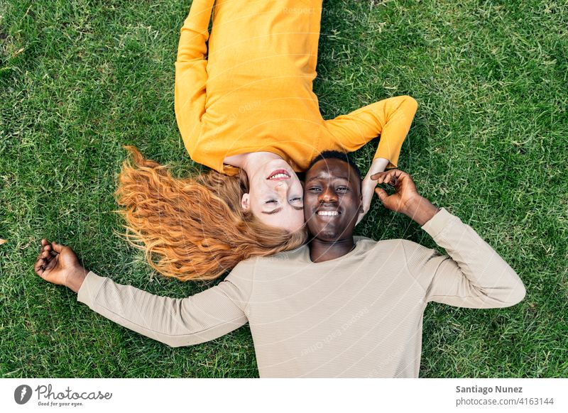 Multiethnic Couple Cuddling in the Grass lying grass having fun top view portrait relationship multi-racial black man caucasian multi-cultural multi-ethnic