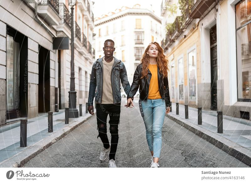 Lovely Couple Holding Hands walking holding hands front view street looking at front portrait relationship multi-racial black man caucasian multi-cultural