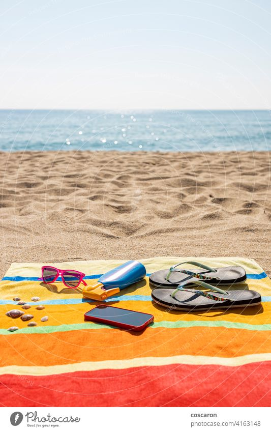 Towel, sunscreen, flip-flops, sunglasses and smart phone on the beach. Summer concept. accessories accessory blue bottle colorful cream fashion holiday journey
