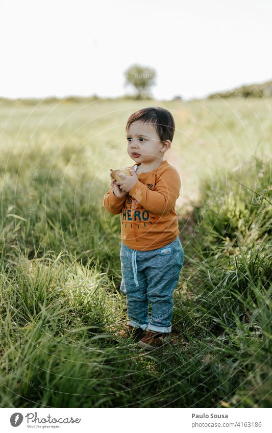 Child eating fruit Boy (child) 1 - 3 years Caucasian Eating Fruit Field Spring Day Colour photo Infancy Toddler Human being Exterior shot Playing Life