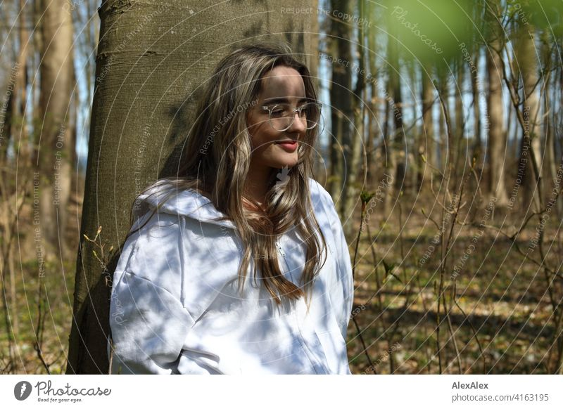 A beautiful blonde girl stands in a forest leaning against a tree and looks sideways into the camera, on her face is a play of light and shadow from the sun and the trees