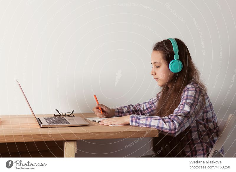 Distance learning at home.Student with a laptop listening to a webinar online with headphones. Elearning concept distance education girl female child childhood