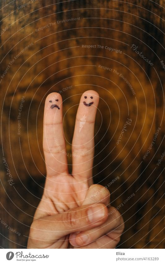 A sad and a happy face painted on the fingers of one hand. Emotions. cheerful two diverse Friendship uneven Relationship disparate at the same time contrary to