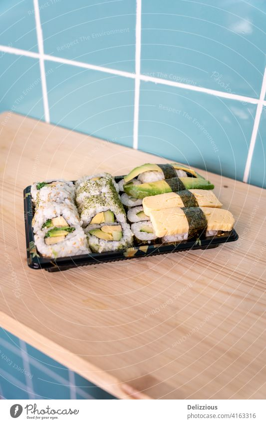 Fresh vegetarian sushi take away on wooden surface and blue tile background food no people nobody healthy healthy diet healthy eating no fish tiles