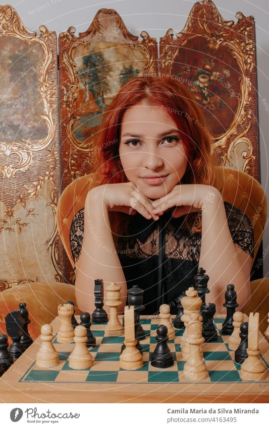 Beautiful girl play chess, queen's gambit play and everyone wins, a smart and pensive face. White and black chess pieces are displayed on the board. Mental game.