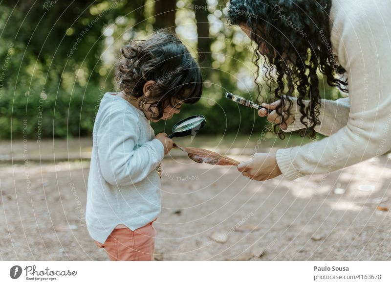 Mother with daughter playing with magnifying glass Magnifying glass motherhood Mother with child Caucasian 1 - 3 years Education explore Magnifying effect