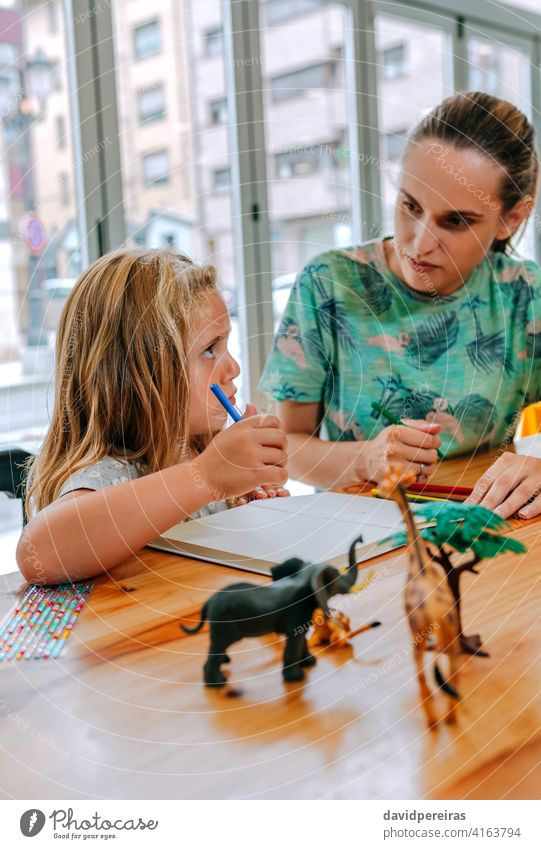 Mother explaining homework to her daughter mother teaching concentrated understand education reconciliation family work quality time study together