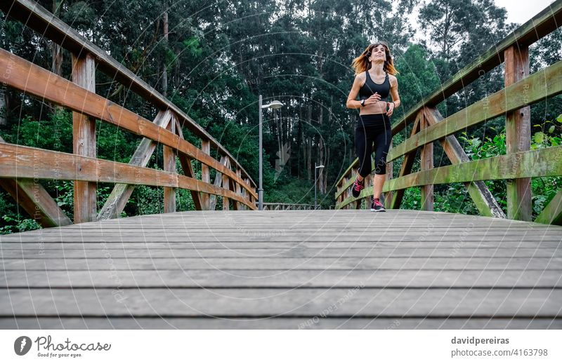 Woman running through an urban park sportswoman tired effort wooden walkway endurance persevere constancy determined athlete cheerful runner fitness female