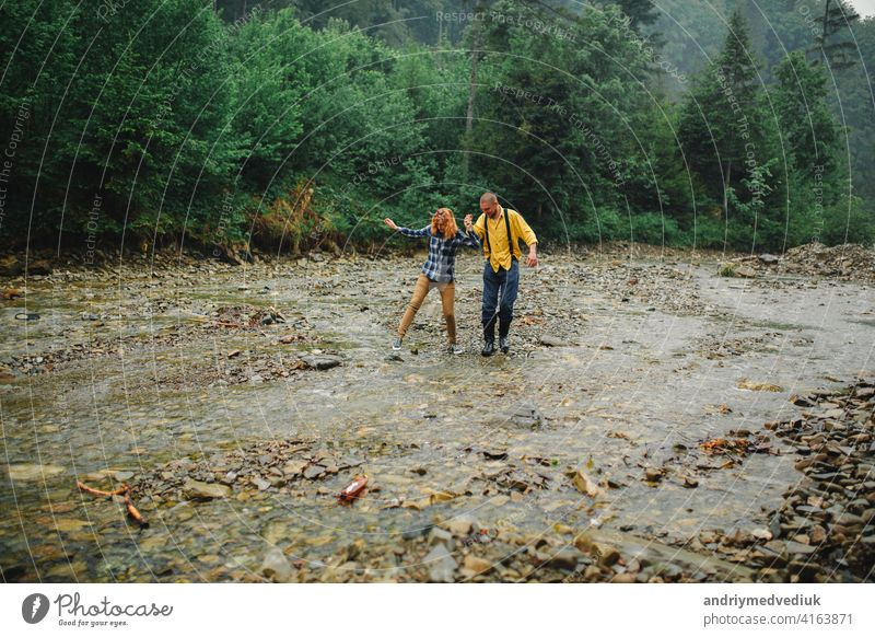 Playful happy handsome couple having while walking in woods. tourists in the mountains. Adventure in nature concept. couple in the mountains active relationship