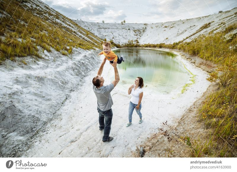 Happy young family near lake, pond. Family enjoying life together at meadow. People having fun in nature. Family bonds outside. Mother, father, child smiling while spending free time outdoors