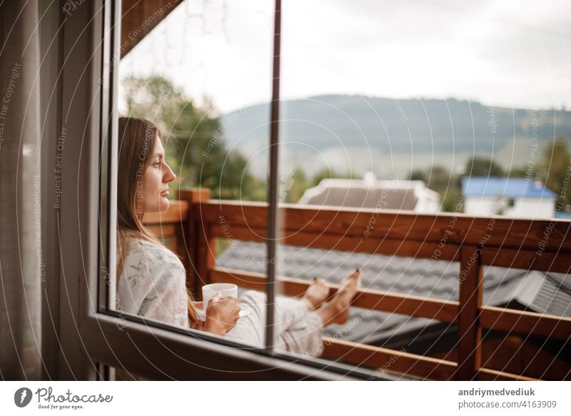 Young female standing after taking a shower in the morning on balcony of the hotel. holding a cup of coffee or tea in her hands. Looking outside nature forest and Mountain