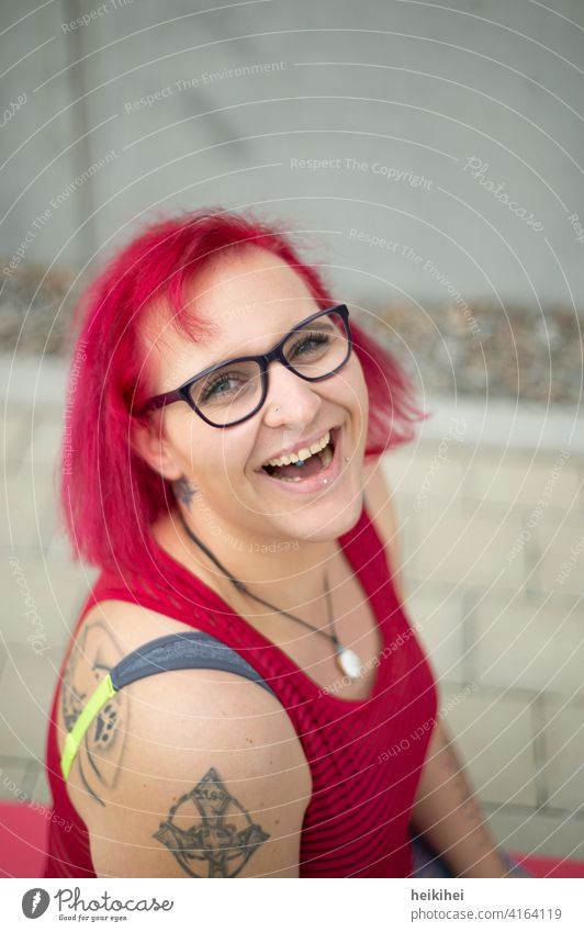 A young redhead woman with glasses and tattoos looks at the camera laughing Woman Eyeglasses Red-haired portrait Lip piercing conspicuous appearance Emanation