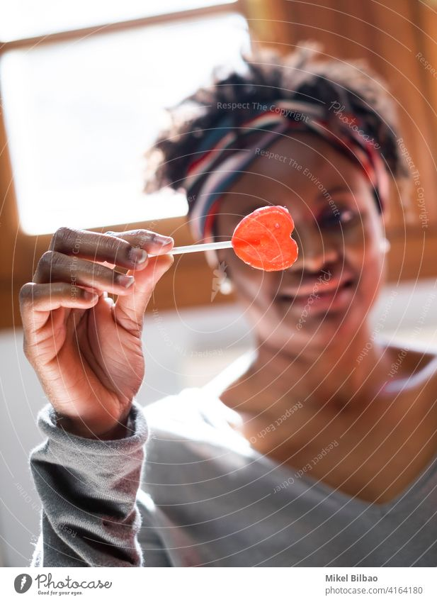 Young black woman at home smiling with a lollipop in her hand beauty african-american people lady model expression hairstyle indoor indoors laughing joy smile