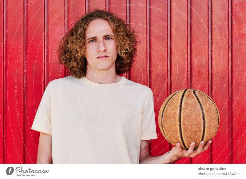 a young man with curly hair and green eyes looking at the camera with a basketball ball in his hand che person sport athletic male game player competitive