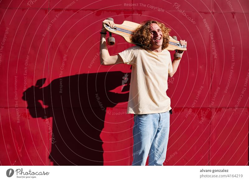 young man with curly hair looking at the camera with his skateboard on his shoulders and a red background longboard che attractive person skateboarding sport