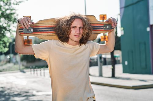 young man with curly hair looking at camera with his longboard or skeateboard on his shoulders in the middle of the street che skateboard attractive person