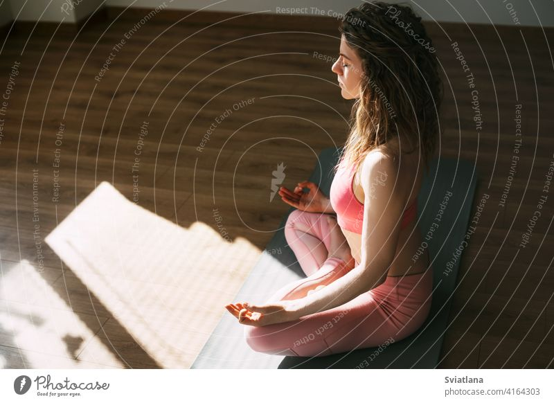 A young girl with her eyes closed meditates in the lotus position in the classroom.Sports, fitness, yoga. Side view, space for text woman meditating exercise