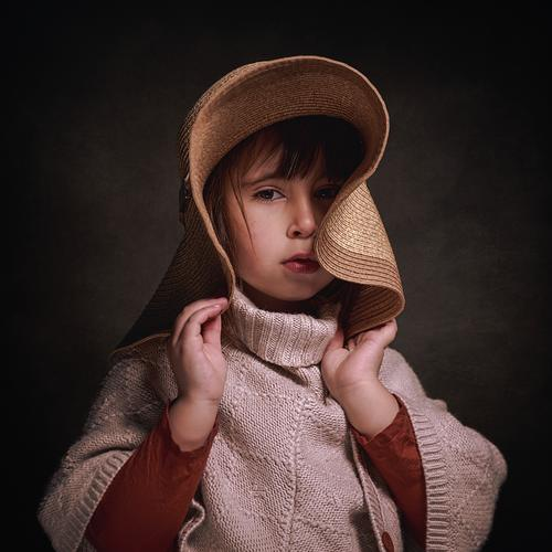 4-year-old Caucasian girl with hat and a cloth poncho. she poses stylish and elegant holding the hat with her hands. square format adorable alone attractive