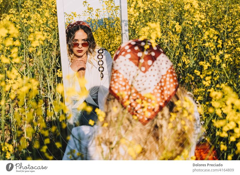 Image of a beautiful woman looking at her reflection in a mirror in a field of spring flowers Beautiful Blonde Sunglasses paradise relax scene summer summertime