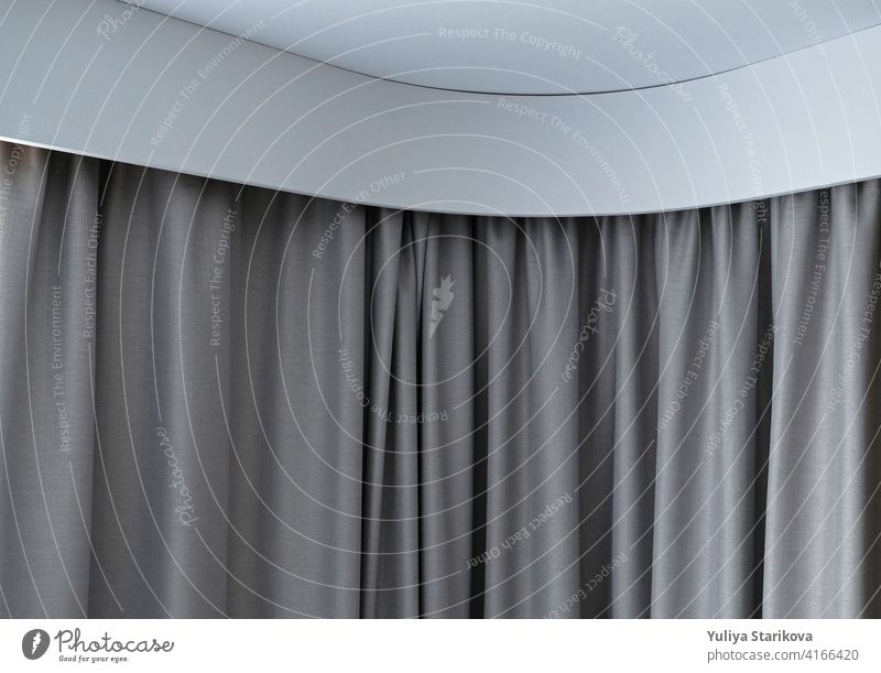 Angular cornice with drapes and white curtain or tulle. Interior details close up. White wall, ceiling, cornice niche, curtains on the window. Corner white plastic hidden curtain rod.