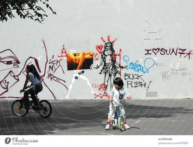 Fantasies in the city Child Girl Bicycle Places Wall (building) Woman Human being Scooter Graffiti Cycling Playing Effortless Exterior shot