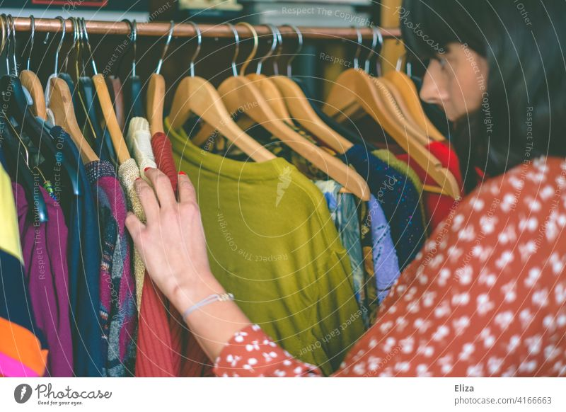 Young woman rummaging through clothes on a clothes rack in a second hand store or flea market. Flea market garments Clothes clothes rail rummage Dresses