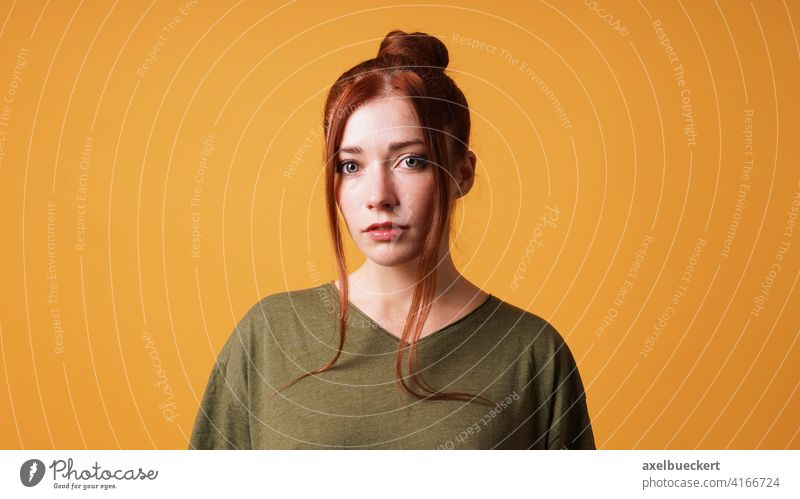 portrait of pretty young woman with red hair bun and curtain bangs person girl redhead red-haired beauty adult beautiful serious face model female caucasian