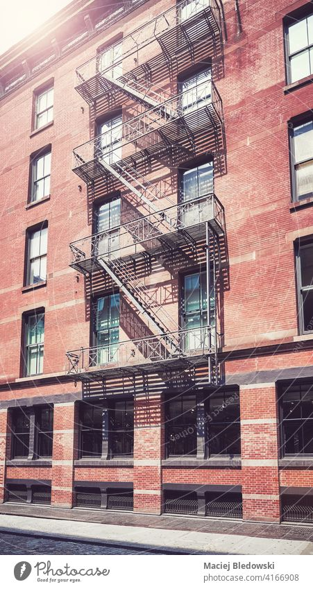 Old brick building with iron fire escape, color toning applied, New York City, USA. city Manhattan old house street apartment architecture stairs cityscape