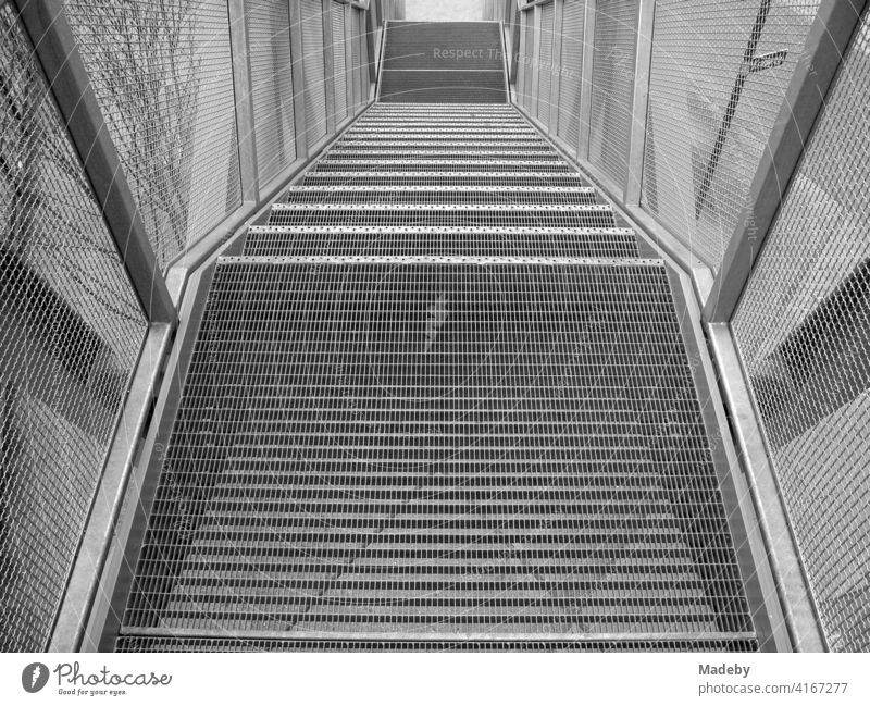 """Staircase made of steel and wire mesh at the observation deck of the harbour crane """"Blauer Kran"""" at the old harbour in Offenbach am Main in Hesse, photographed in traditional black and white"""
