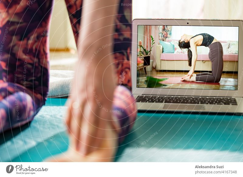 Beautiful fit woman streaming broadcast video blog about yoga and fitness in living room. Healthy lifestyle and social media. Woman watching video tutorials on laptop and working out at home.
