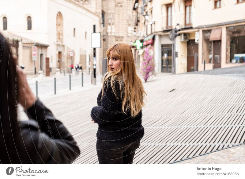 Young brunette girl taking a photo of blonde girl in an urban space. old city vintage camera photography tourist travel destination vacations posing model