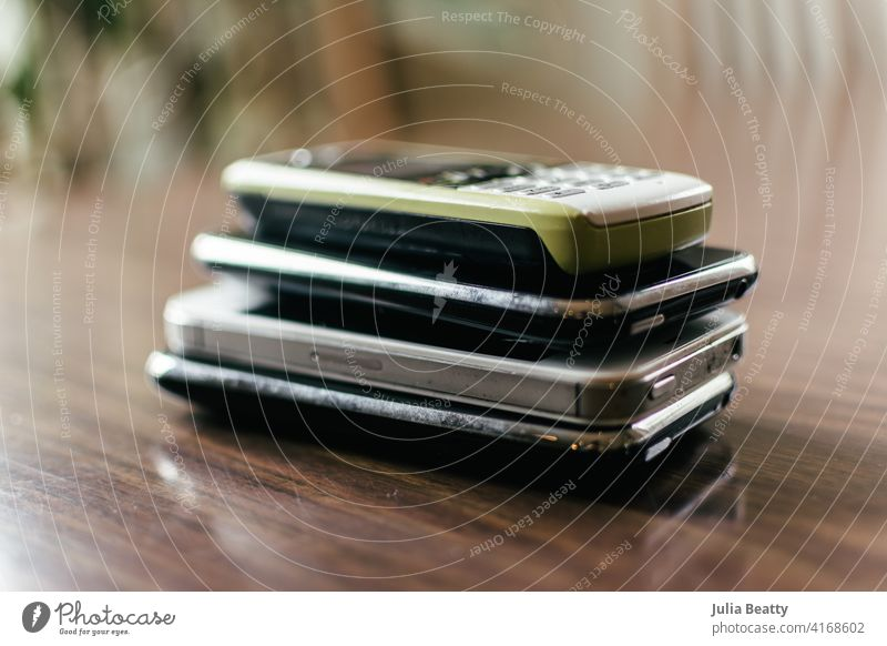 Stack of four old cellphones on a dining room table; top phone is green outdated cellular hold mobile wireless recycle e-cycle trash garbage collect collection