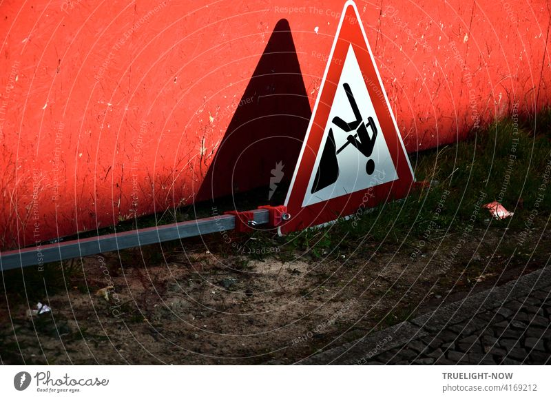 End of work at the construction site: Construction workers have laid the warning sign with a black pictogram framed in red on a white background flat on the sandy ground in front of a red construction fence illuminated by the shadows cast by the evening sun.