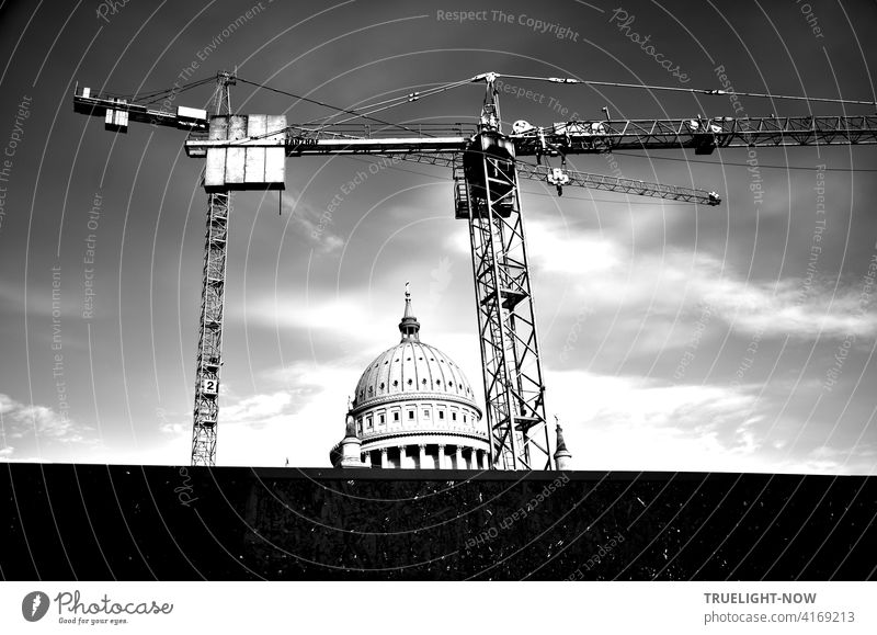 A construction crane and another construction crane behind a dark screen wall form the frame around the round tower of the Nikolai church, a landmark of Potsdam, in front of a slightly cloudy sky.