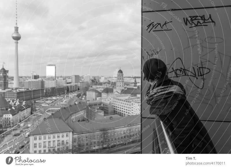 a woman looks out of the balcony in the direction of the television tower Television tower Middle fishing island City hall High-rise Balcony Berlin TV Tower