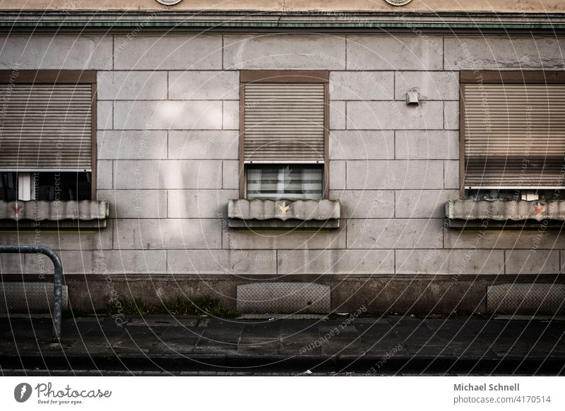 Facade and windows of an old grey apartment building Gloomy dreariness Old Gray roller shutter Window Building Architecture Apartment Building Exterior shot
