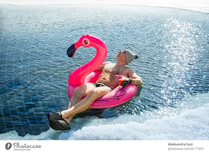 A man swimming in an ice hole in winter in Finland, floating on a pink inflatable flamingo with cocktail in hand. Vacation options, dreaming of summer. active