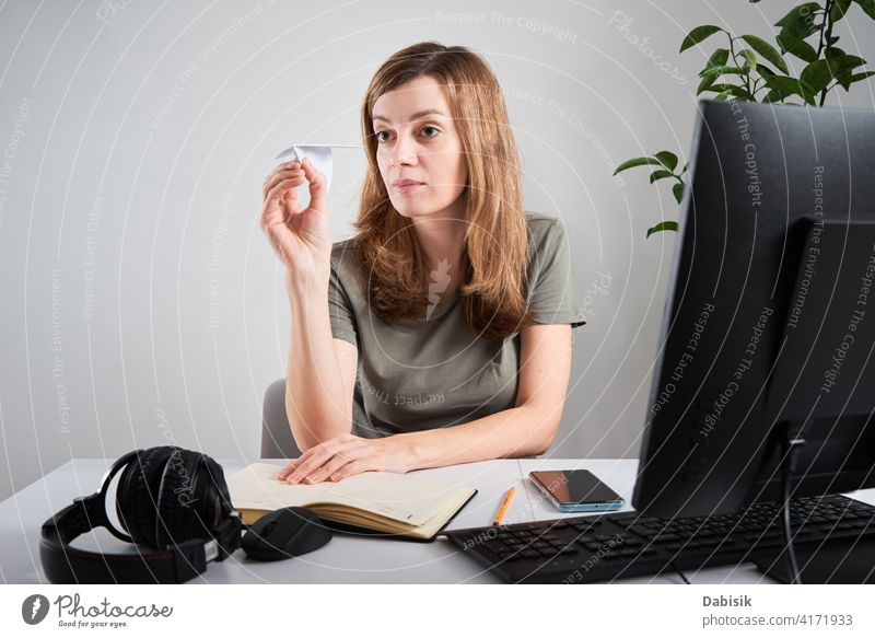 Woman hold paper plane while working at home office procrastinate freelance online woman lazy business workspace computer organization creative planning