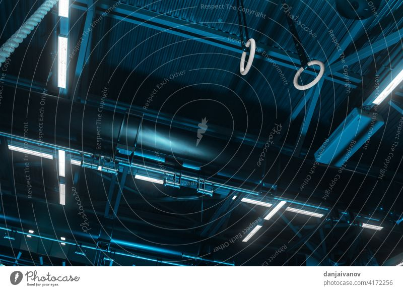 gymnastics rings on the ceiling of the gym activity arena athleticism backgrounds blue bright light competition competitive sport equipment flooring