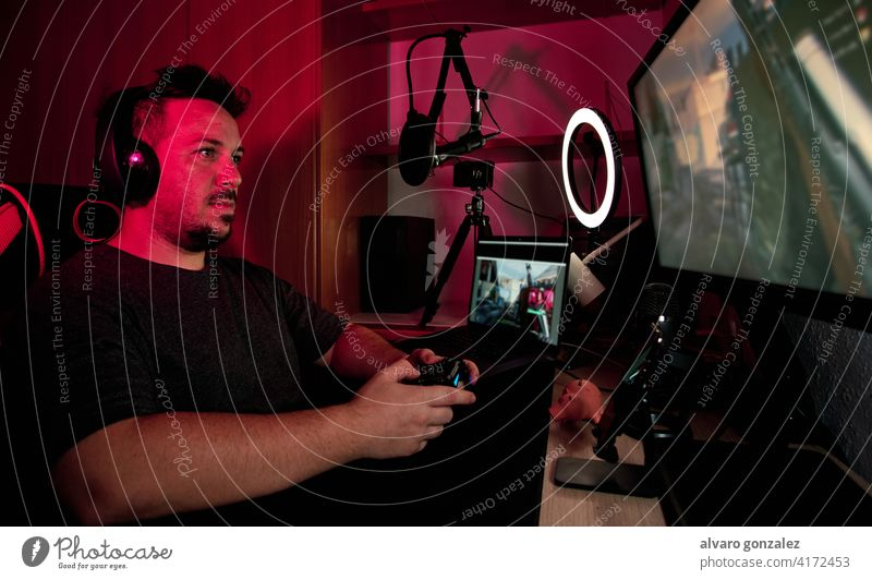 a gamer playing and streaming live with microphones and cameras internet gaming headphones online technology che headset computer person tournament room player
