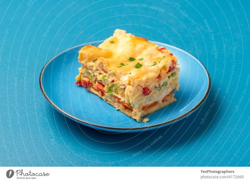 Vegetarian lasagna on a blue plate. Single portion of lasagna background baked bechamel sauce cheese close-up cooked copy space cuisine cut out delicious dinner