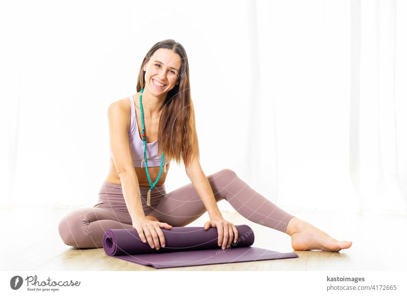 Young sporty female yoga instructor in bright white yoga studio, smiling cheerfully while rolling the yoga mat after yoga session. Smiling, looking at camera.