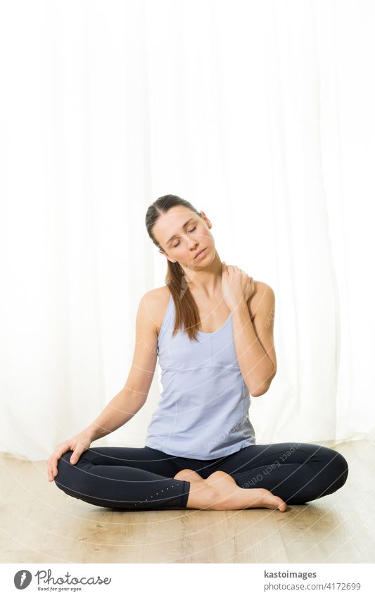 Portrait of gorgeous active sporty young woman practicing breathing exercises in yoga studio. Healthy active lifestyle, working out indoors in gym wellness pose