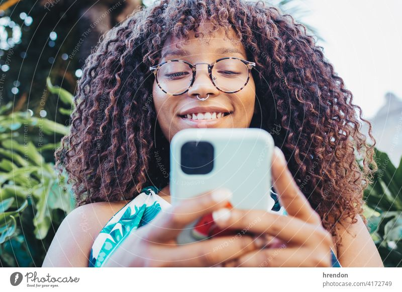 African girl's close-up using her smartphone female woman african hair face communication young technology black cellphone telephone joy smile mobile afro