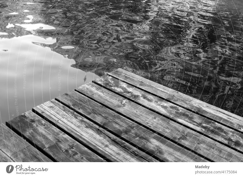 Old wooden footbridge for bathers in summer at the Mittersee in Füssen in the Ostallgäu in the Free State of Bavaria, photographed in classic black and white