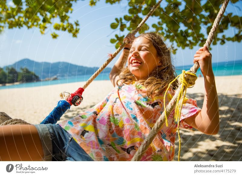 Happy cute little girl laughing and swinging on swing on the tree at the beach. Beautiful summer sunny day, turquoise sea, rocks, white sand, picturesque tropic landscape. Phuket, Thailand. Carefree
