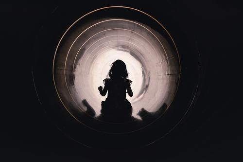 Child slides through a slide tube on the playground Dress Girl Slide Playground Tunnel trust courageous overcome Light at the end of the tunnel Pipeline conduit