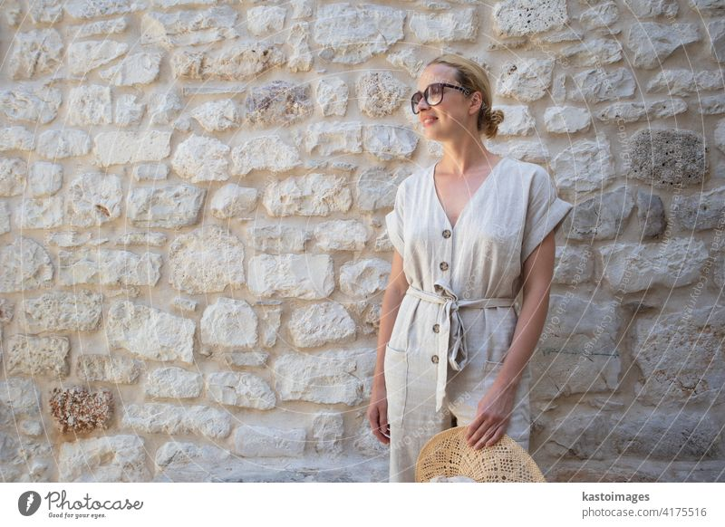 Portrait of beautiful cheerful blonde woman wearing one piece sundress and summer hat, standing in front of old medieval stone wall. Summer vacation portrait concept. Copy space.