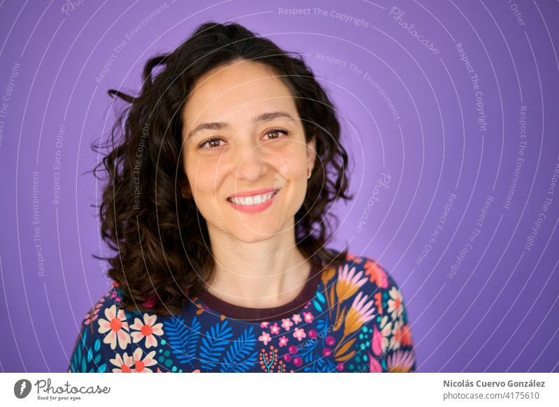 Beautiful young woman smiling to the camera over isolated purple background. Curly hair style. Wearing colorful handmade sweater. portrait person beauty girl