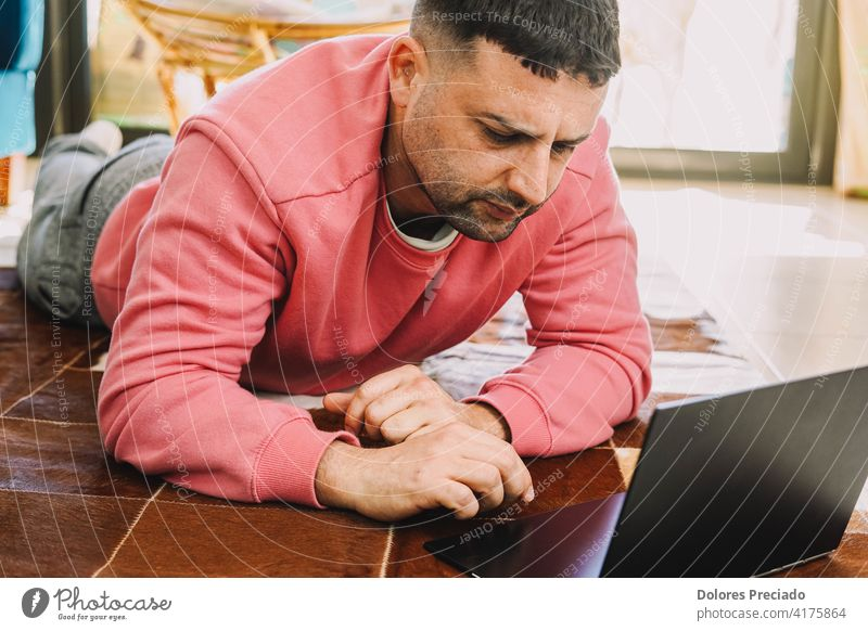 Man teleworking on a carpet in his living room with his computer due to the coronavirus pandemic typewriter pijama caucasian male person people home office